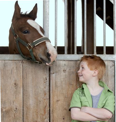 Junge vor Pferdestall mit Pferd